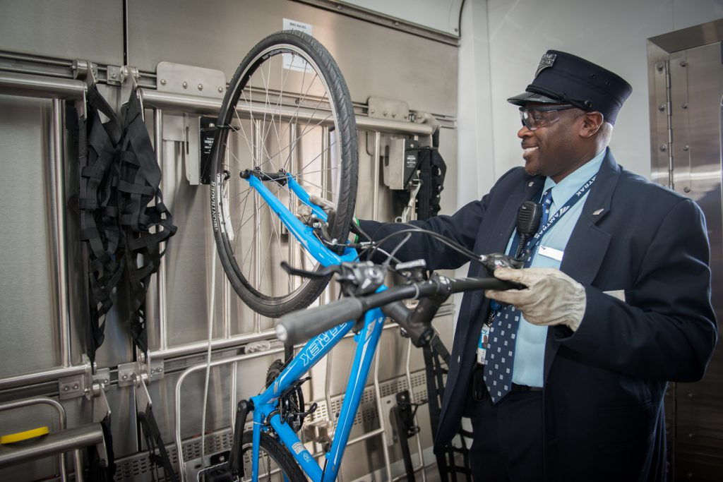 An conductor loads a bicycle on board one of North Carolina's Amtrak trains.