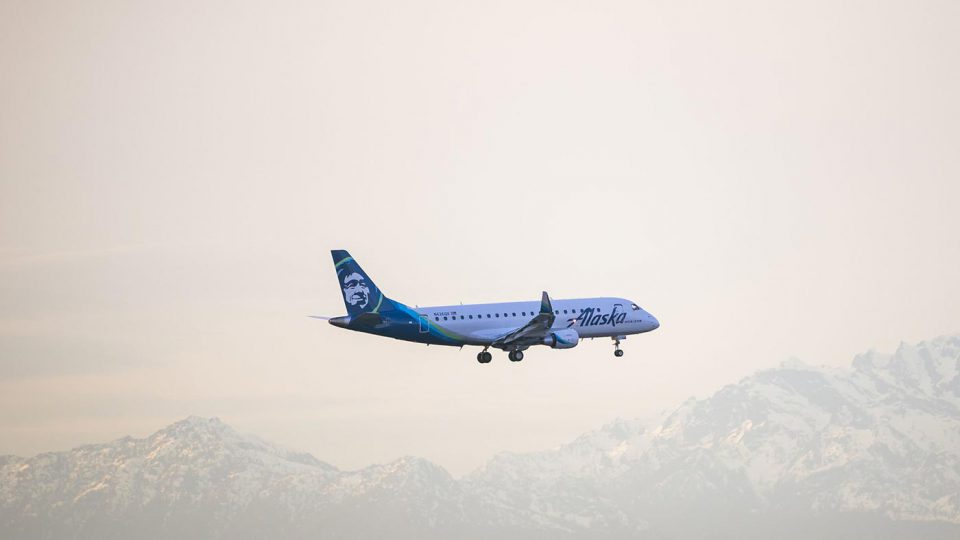 Blue and white Alaska Airlines plane landing with mountains in the background.