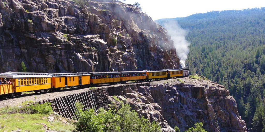 Durango and Silverton Railroad steaming along side mountain side.