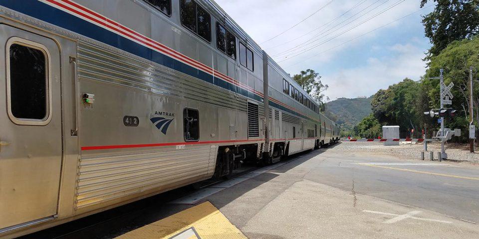 Amtrak train at railroad crossing.