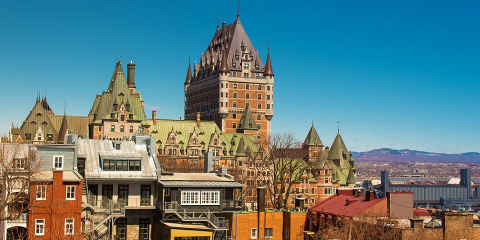 Historic red brick towered building sitting atop a hill surrounded by colorful homes and buildings in Quebec City, Canada.