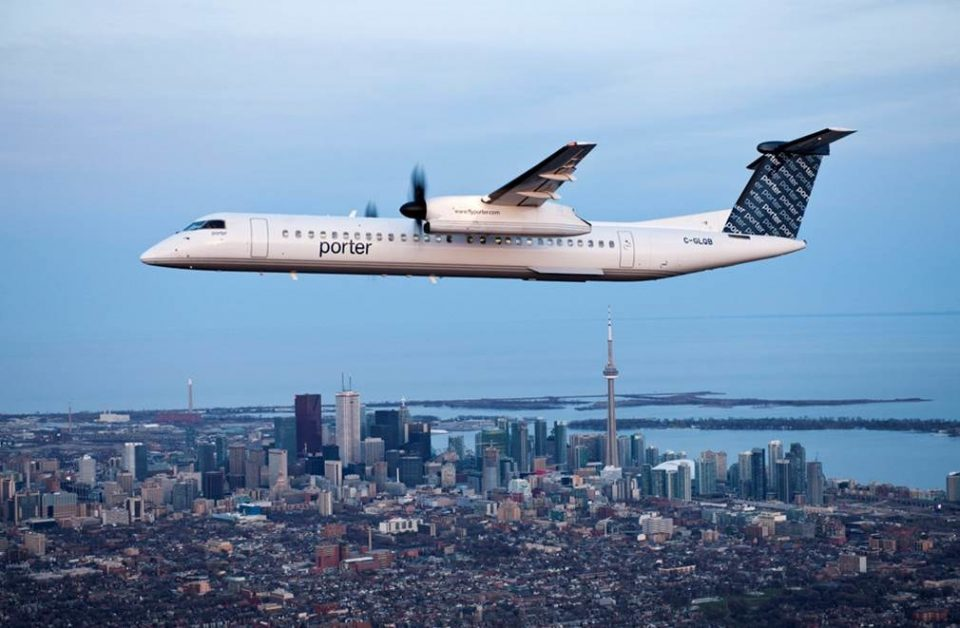 Porter Airlines aircraft flying with the Toronto skyline in the background.