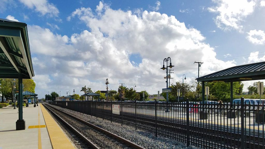 Train station platform with blue skies and white clouds in the background.