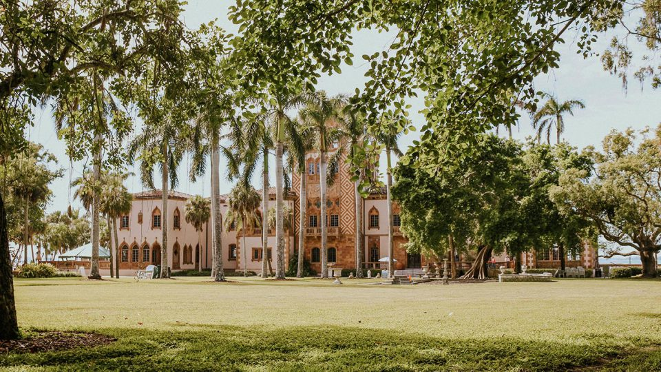 Tan colored Spanish-designed building sitting on the grounds with a large green yard and palm trees.