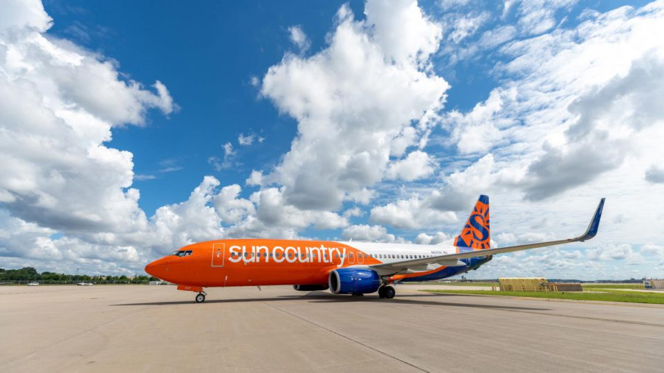 Sun Country's orange, white, and blue Boeing 737 on runway.