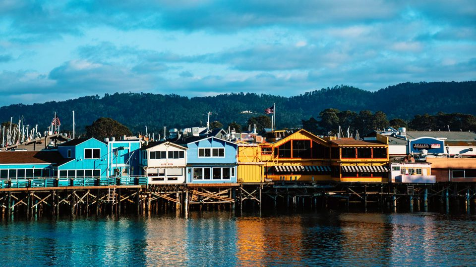 Colorful wooden buildings stand on a wharf along a harbor.