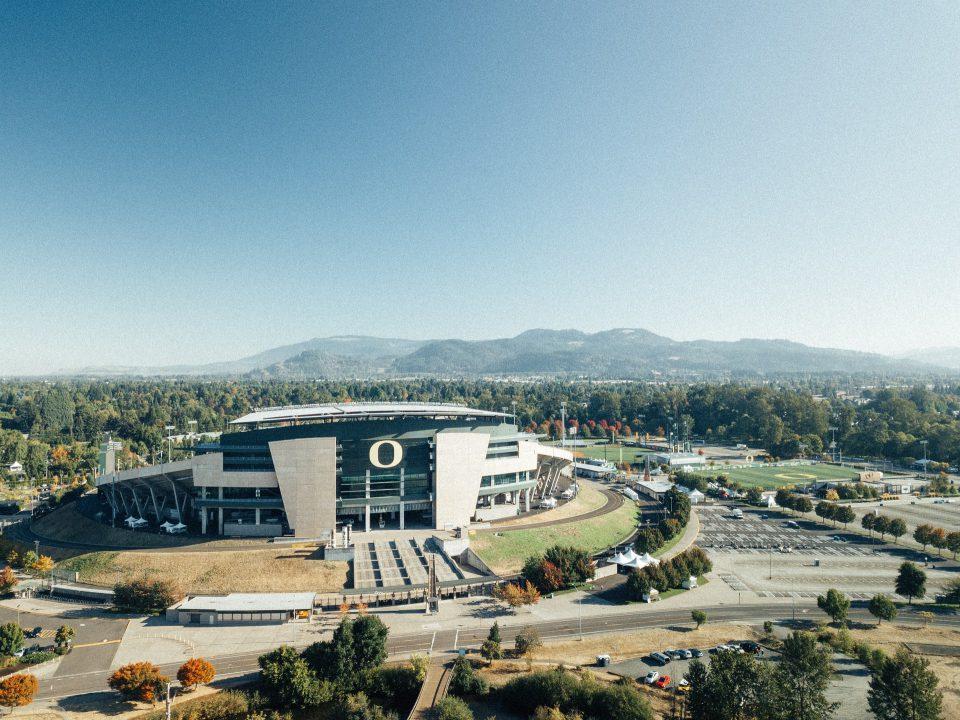Modern Oregon stadium against hilled background.