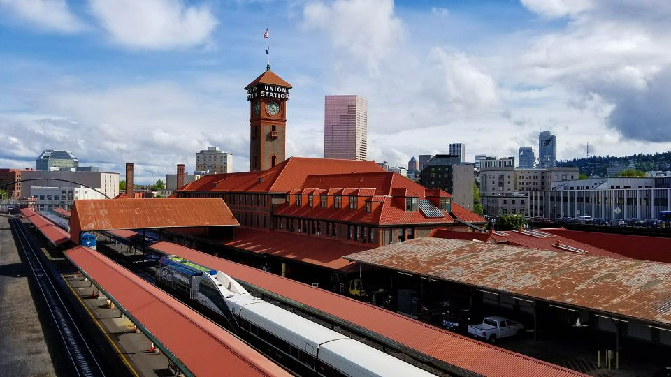Red roofed train station against a modern city skyline.